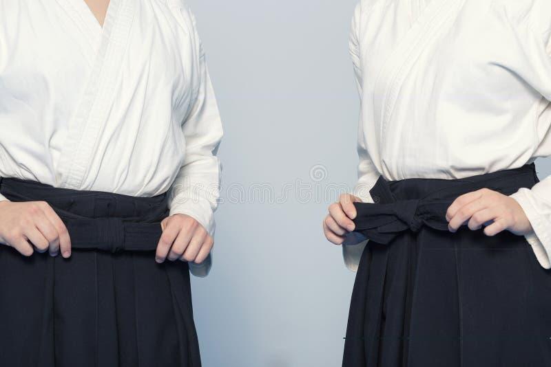 As mãos da menina amarram um hakama imagens de stock royalty free