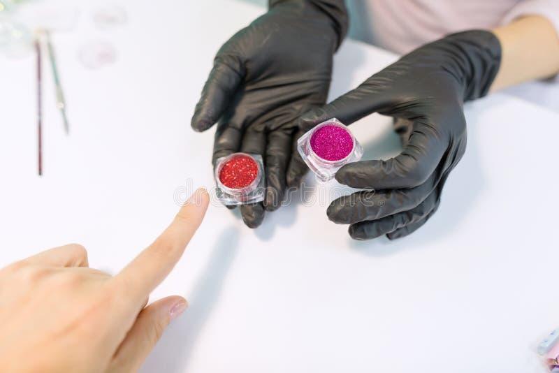 As mãos da mostra do manicuro sparkles, cristais para pregos foto de stock