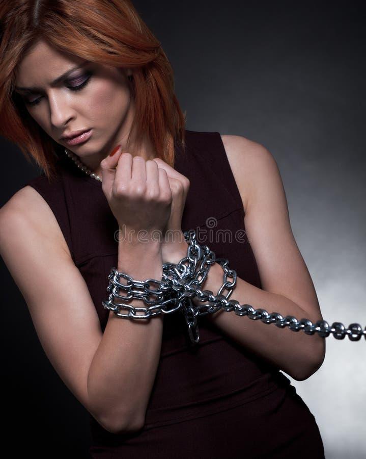 As mãos da mulher amarradas junto com correntes foto de stock royalty free