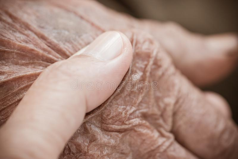 As mãos da mulher asiática que guardam as mãos de primeira geração idosas pobres do homem enrugaram a pele com o sentimento para  imagens de stock