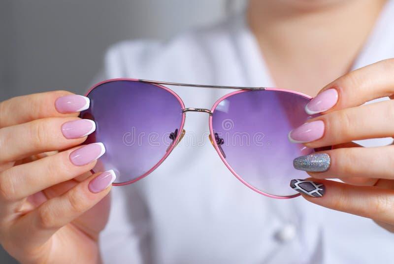 As mãos da mulher com um tratamento de mãos bonito examinam óculos de sol fotos de stock royalty free