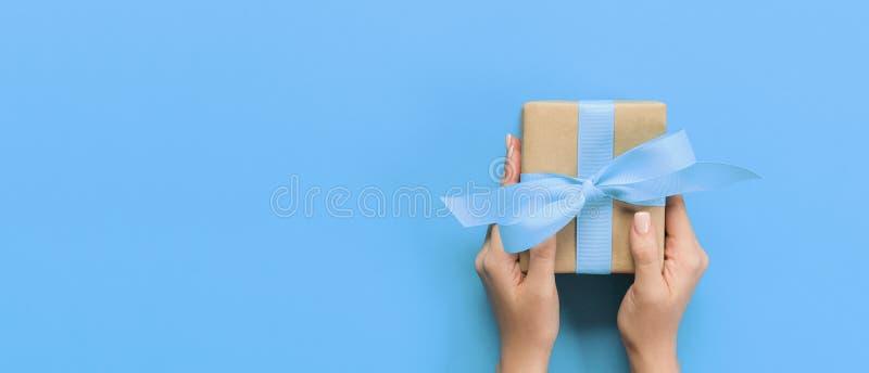 As mãos da mulher dão o Valentim envolvido ou o outro presente feito a mão do feriado no papel com fita roxa Caixa atual, decoraç fotos de stock royalty free