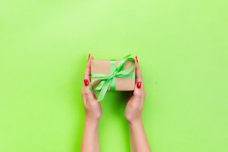 As mãos da mulher dão o Valentim envolvido ou o outro presente feito a mão do feriado no papel com fita verde Caixa atual, decora fotografia de stock royalty free