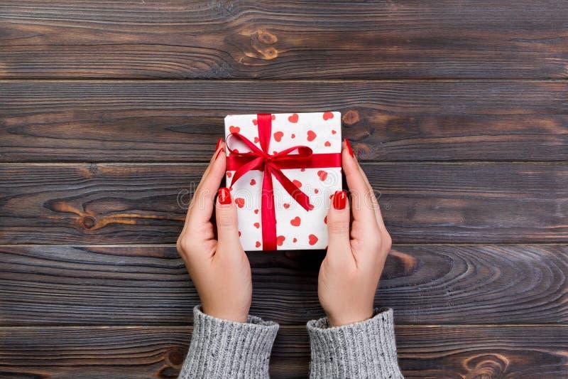 As mãos da mulher dão o Valentim envolvido ou o outro presente feito a mão do feriado no papel com fita vermelha Caixa atual, dec imagens de stock