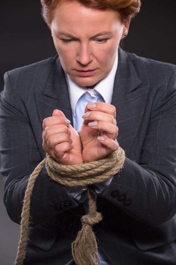 As mãos da mulher de negócios amarradas acima com corda foto de stock