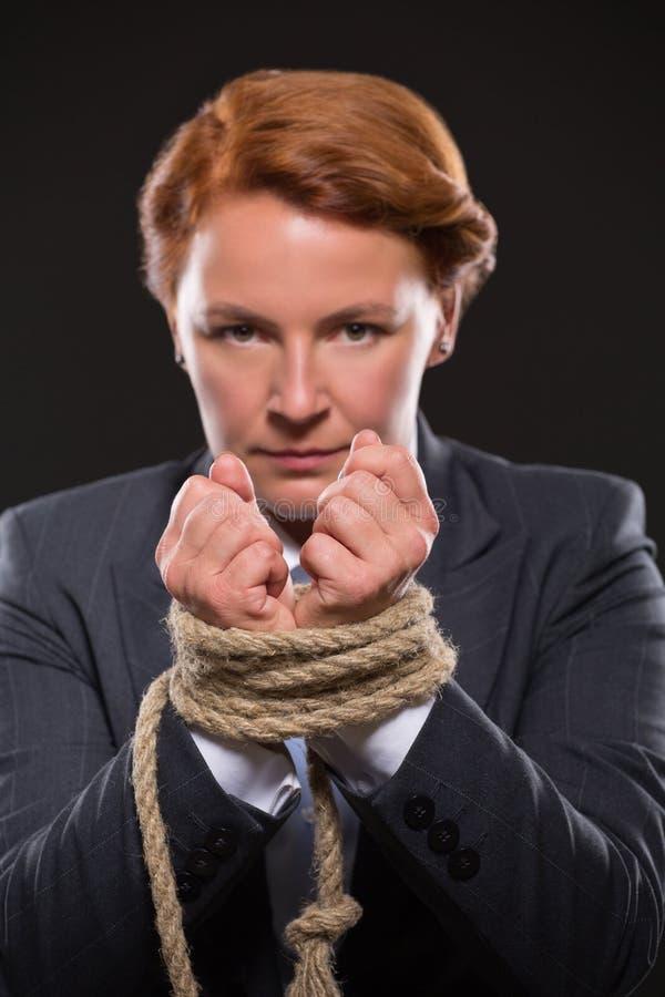 As mãos da mulher de negócios amarradas acima com corda imagem de stock royalty free