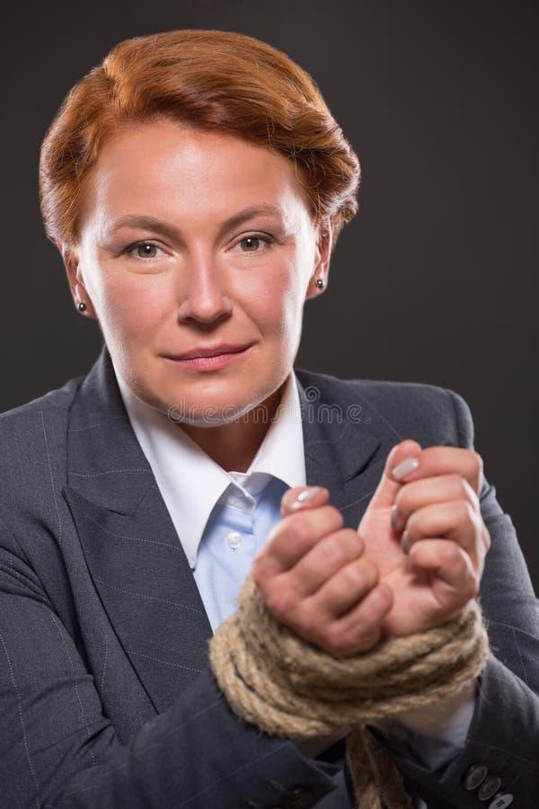 As mãos da mulher de negócios amarradas acima com corda fotografia de stock royalty free