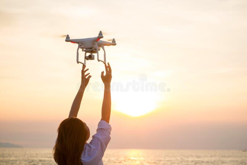 As mãos da mulher do zangão e do fotógrafo do UAV Voo do helicóptero do zangão com câmara digital imagens de stock royalty free