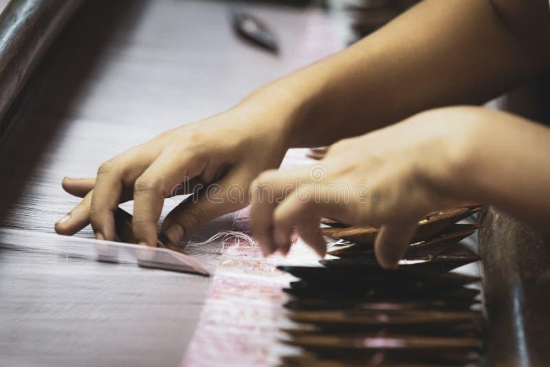 As mãos da mulher em um processamento de matéria têxtil antigo Tecer é a arte de construir uma tela imagens de stock royalty free