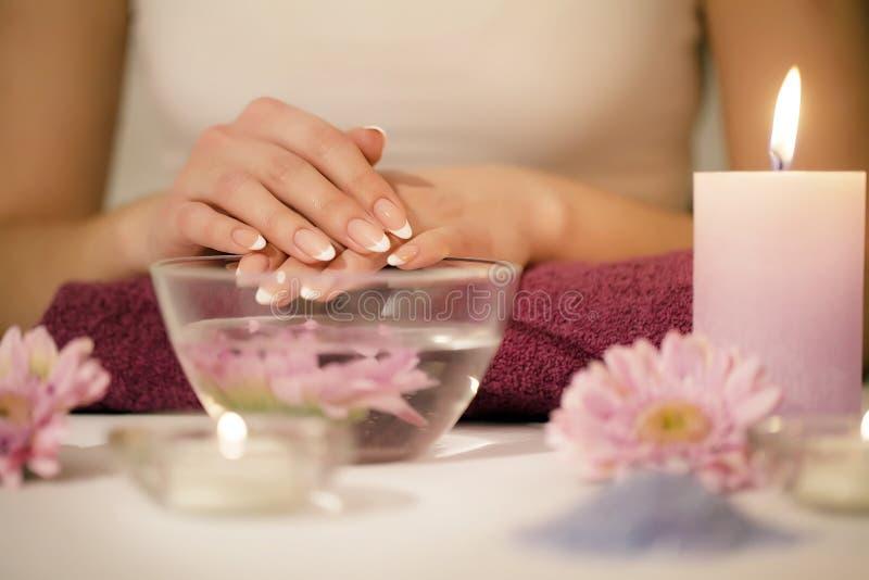 As mãos da mulher em um salão de beleza do prego que recebe uma mão esfregam a casca pela fotografia de stock