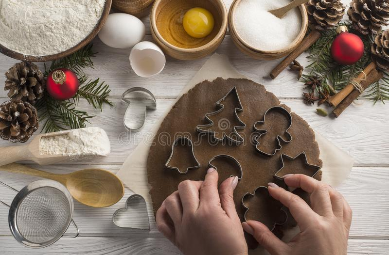 As mãos da mulher fazem cookies do Natal em um fundo de madeira branco, espaço da cópia Vista superior fotos de stock royalty free