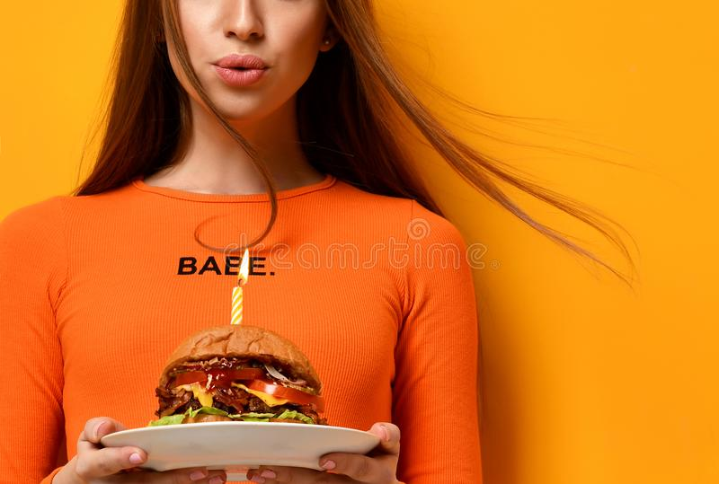 As mãos da mulher guardam o sanduíche grande do assado do hamburguer com carne e vela iluminada para a festa de anos no amarelo imagem de stock royalty free