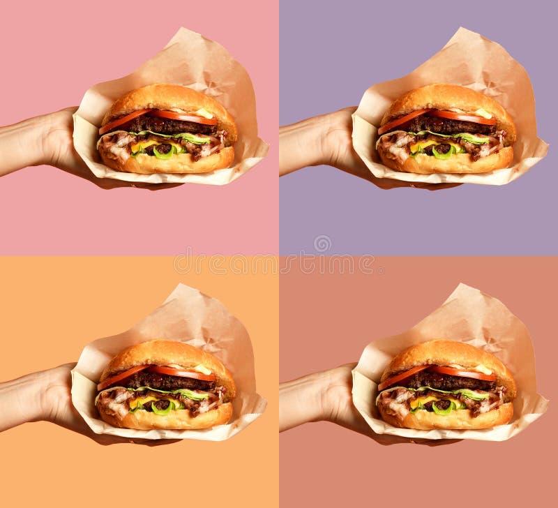 As mãos da mulher guardam o sanduíche grande do assado do hamburguer do queijo com carne de mármore no roxo foto de stock royalty free