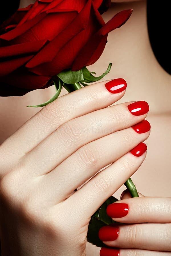 As mãos da mulher manicured bonita com verniz para as unhas vermelho Beautifu imagem de stock