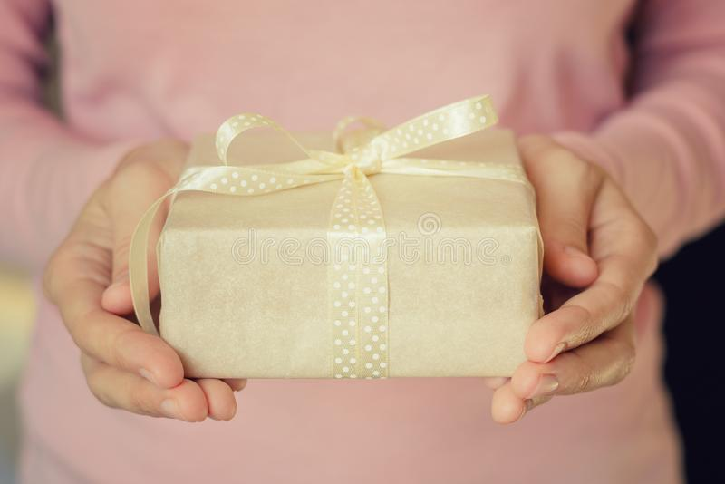 As mãos da mulher mantêm uma caixa de presente envolvida no papel com fita imagem de stock royalty free