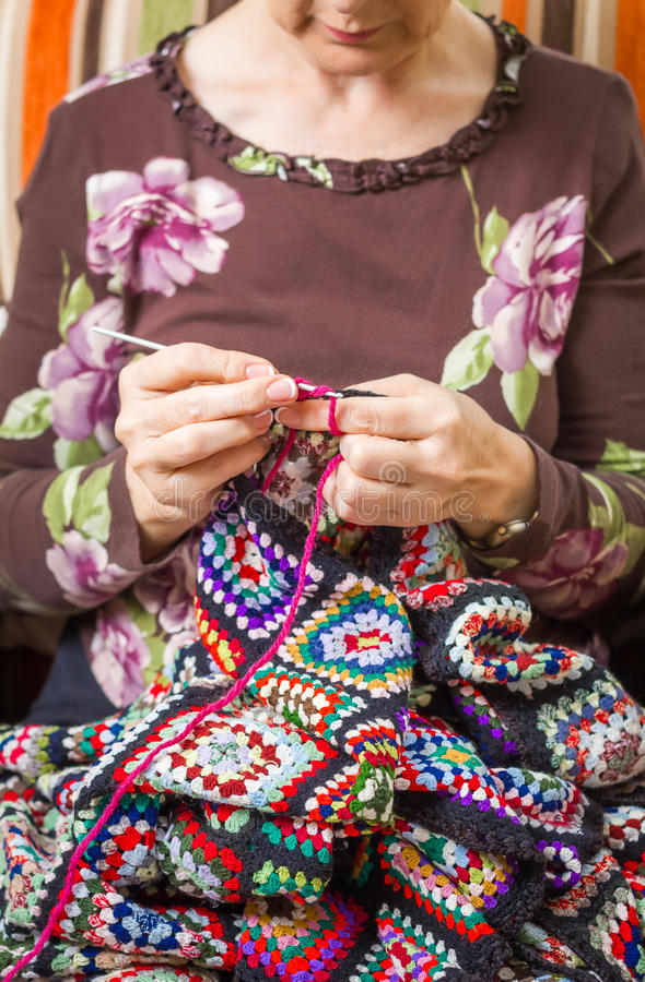 As mãos da mulher que fazem malha uma lã do vintage estofam foto de stock royalty free