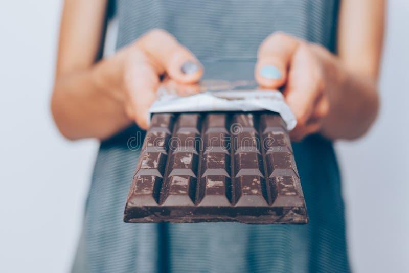 As mãos da mulher que guardam a barra de chocolate escura desempacotada fotografia de stock