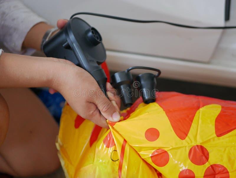 As mãos da mulher que guardam e que usam a mini bomba de ar, conectada à tomada do carro, para inflar uma boneca de balanço fotos de stock