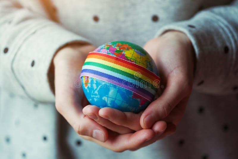 As mãos da mulher que guardam o globo com a fita do arco-íris de LGBT foto de stock royalty free