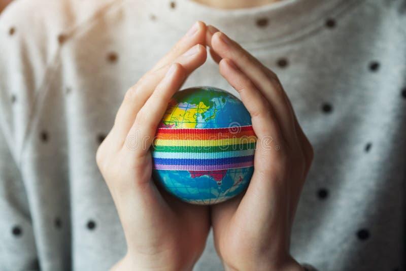 As mãos da mulher que guardam o globo com a fita do arco-íris de LGBT imagem de stock royalty free