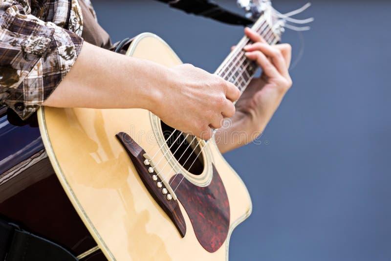 As mãos da mulher que jogam o close up da guitarra acústica foto de stock