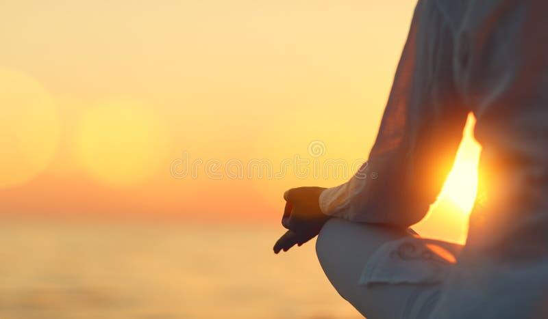 As mãos da mulher que meditam na ioga levantam no por do sol na praia imagem de stock royalty free