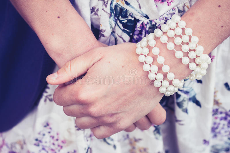 As mãos da mulher que vestem um bracelete da pérola imagens de stock royalty free