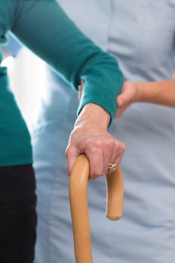 As mãos da mulher superior no trabalhador da vara de passeio com cuidado em Backgro imagens de stock