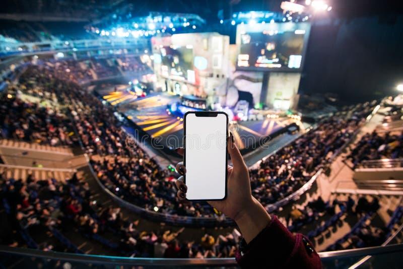 As mãos da mulher usando a aplicação digital no telefone esperto móvel no evento do esport na arena grande Copie o espaço foto de stock royalty free