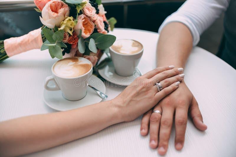 As mãos da posse dos noivos, guardando as alianças de casamento caras com ouro branco, no fundo de um ramalhete do casamento fotografia de stock royalty free