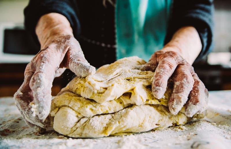 As mãos da senhora italiana idosa que fazem a massa italiana em casa feita imagens de stock royalty free