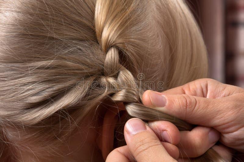As mãos da tecelagem da mulher trançam sua filha fotografia de stock