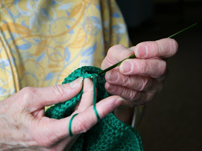As mãos das avó fazem crochê o fio verde Grampo do close up do crochê superior da mulher foto de stock