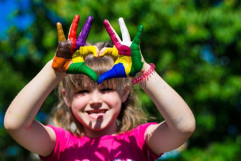 As mãos das crianças em pinturas da cor fazem uma forma do coração, foco nas mãos fotos de stock