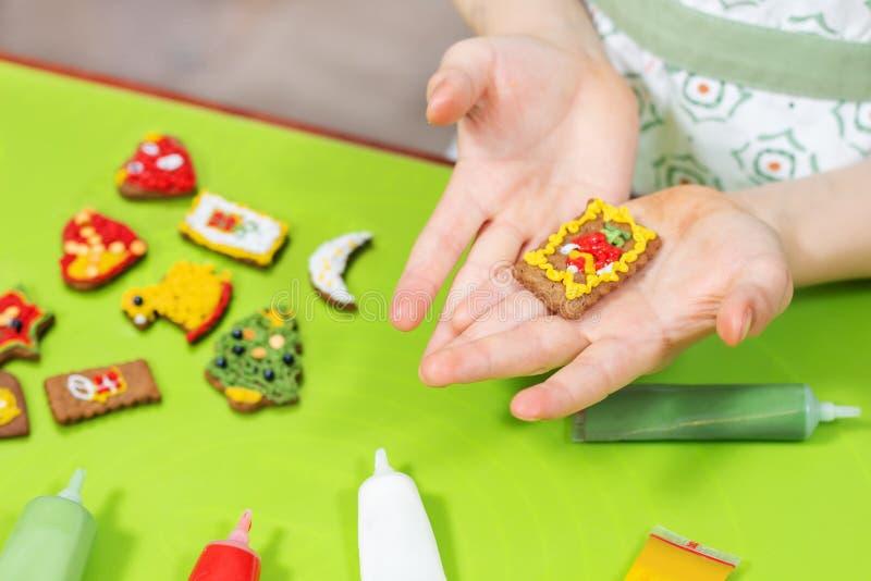 As mãos das crianças estão guardando um bolo retangular decorado Os bolos coloridos da canela encontram-se na tabela verde no fun imagens de stock royalty free