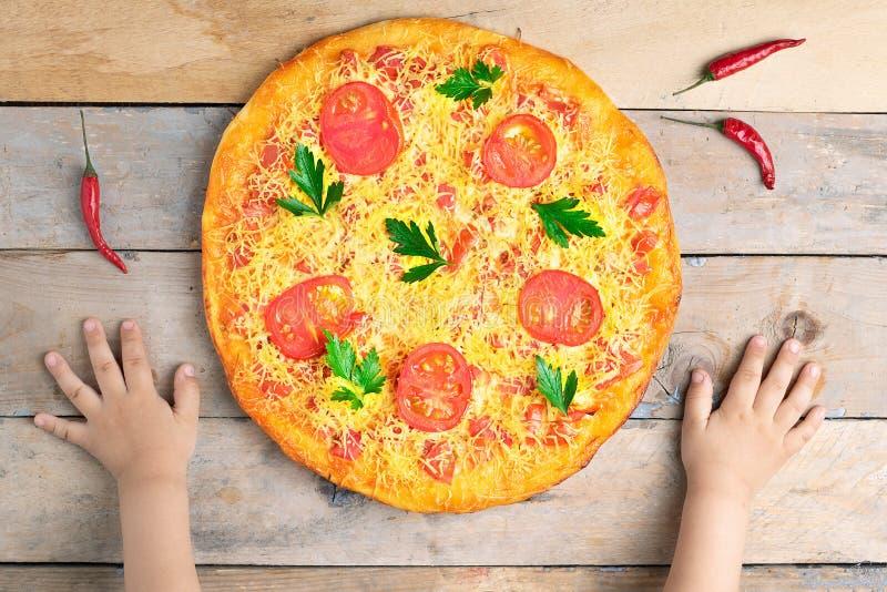 As mãos das crianças guardam a pizza do margarita do queijo com tomates e manjericão, refeição na tabela rústica de madeira, vist fotografia de stock
