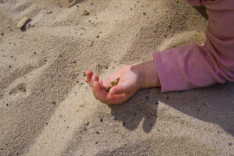 As mãos das crianças na areia ao jogar fotos de stock