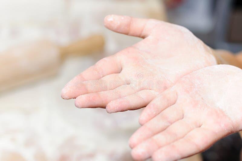 As mãos das crianças na farinha Coza bolos em casa foto de stock