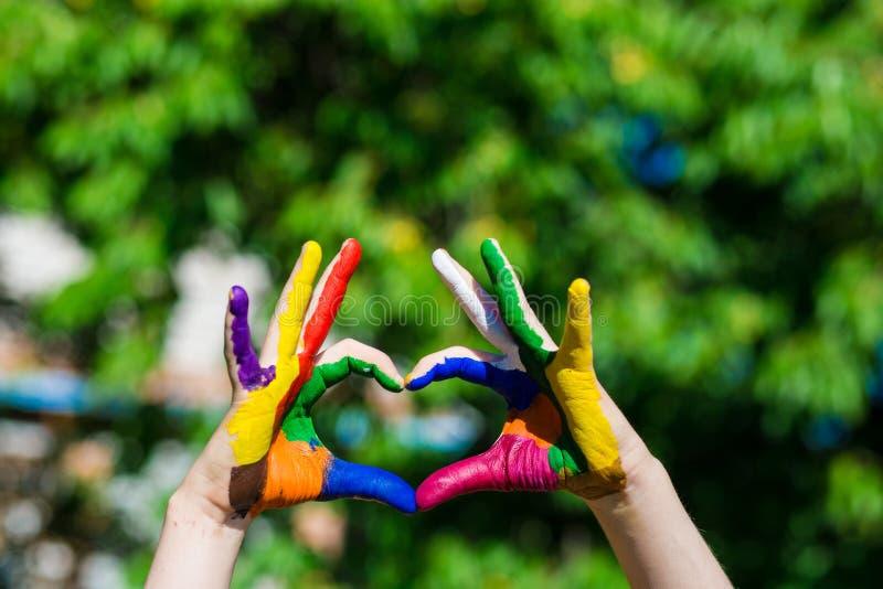 As mãos das crianças pintadas em cores brilhantes fazem uma forma do coração no fundo da natureza do verão foto de stock royalty free