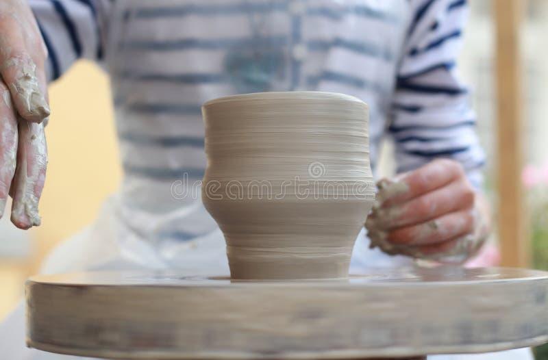 As mãos das crianças que criam o vaso novo imagens de stock
