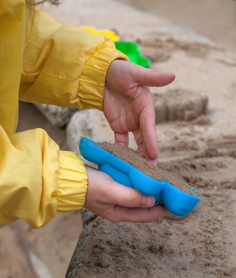 As mãos das crianças que jogam com areia em uma caixa de areia fotografia de stock