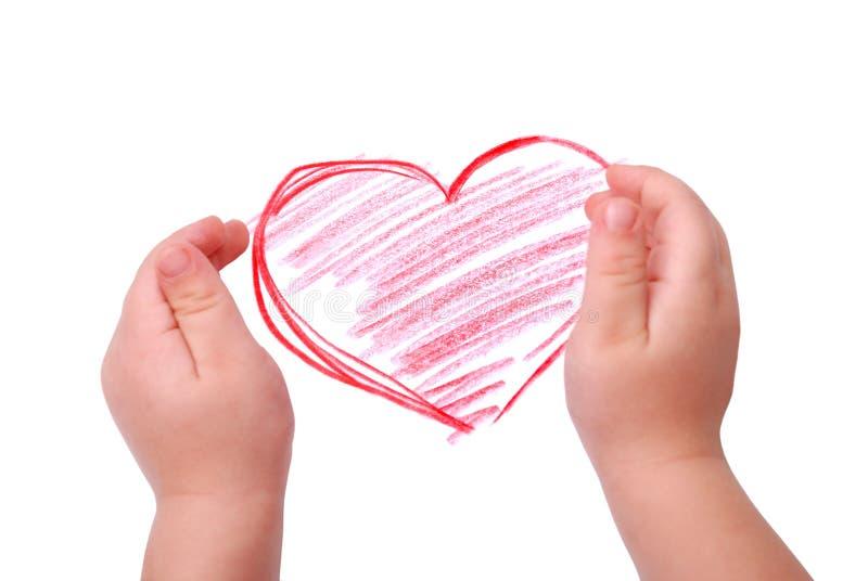 As mãos das crianças são posicionadas no desenho do coração imagens de stock