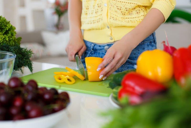 As mãos das donas de casa durante o cozimento da salada foto de stock royalty free