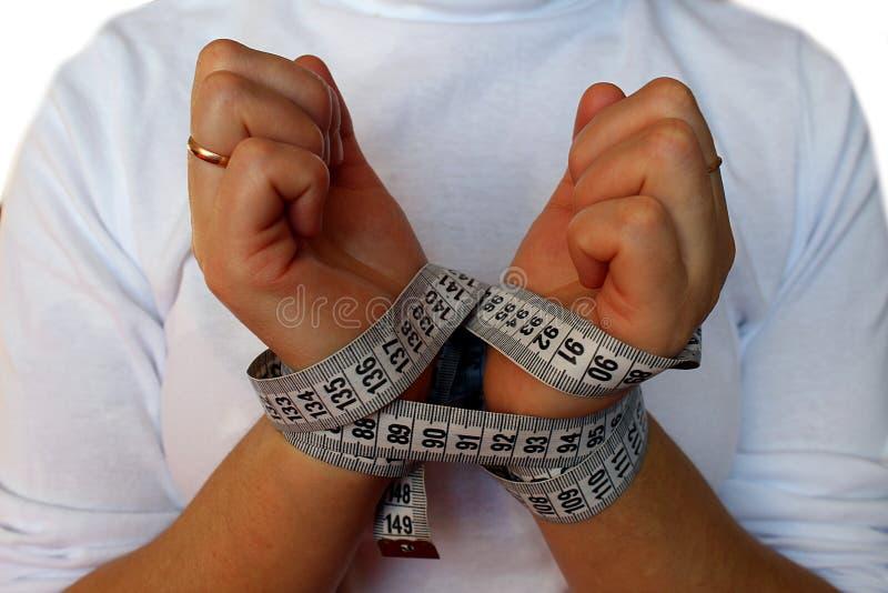 As mãos das mulheres amarraram com uma fita de medição imagem de stock royalty free