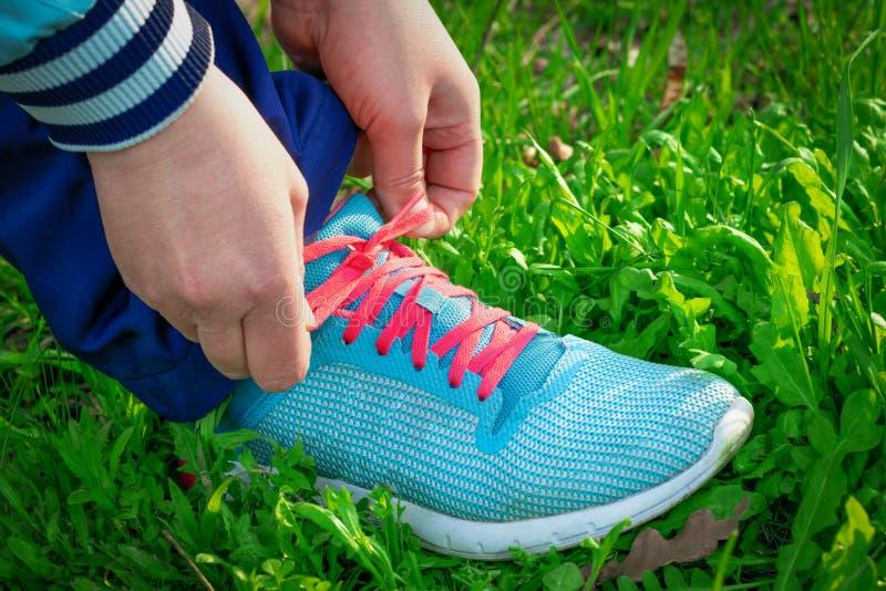 As mãos das mulheres atam acima o laço cor-de-rosa nas sapatas azuis dos esportes no fundo da grama verde fotografia de stock