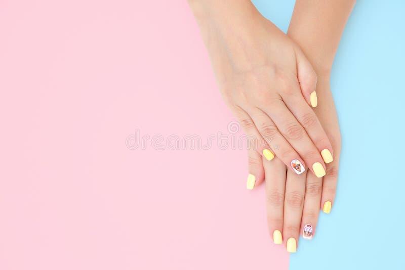 As mãos das mulheres com um tratamento de mãos bonito com os desenhos dos bolos e das cerejas em um rosa e em um fundo azul fotos de stock