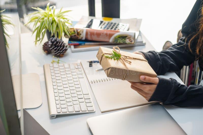As mãos das mulheres de negócio que guardam a caixa de presente pequena na tabela do escritório, que olha a caixa de presente env fotos de stock