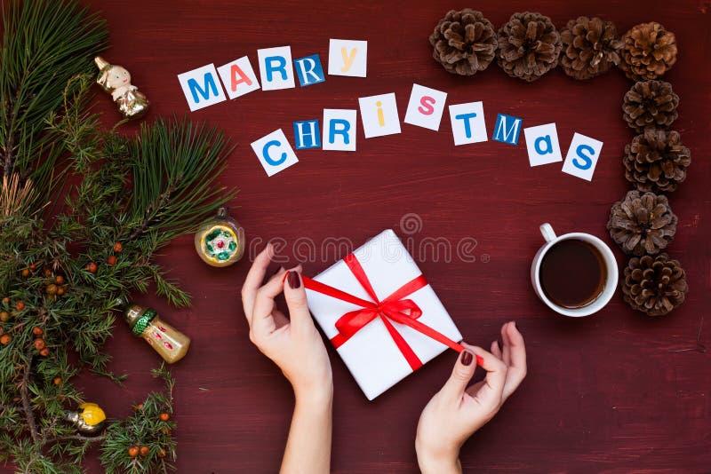 As mãos das mulheres guardam o fundo do café do feriado do ano novo do Natal da árvore de Natal do presente imagens de stock royalty free