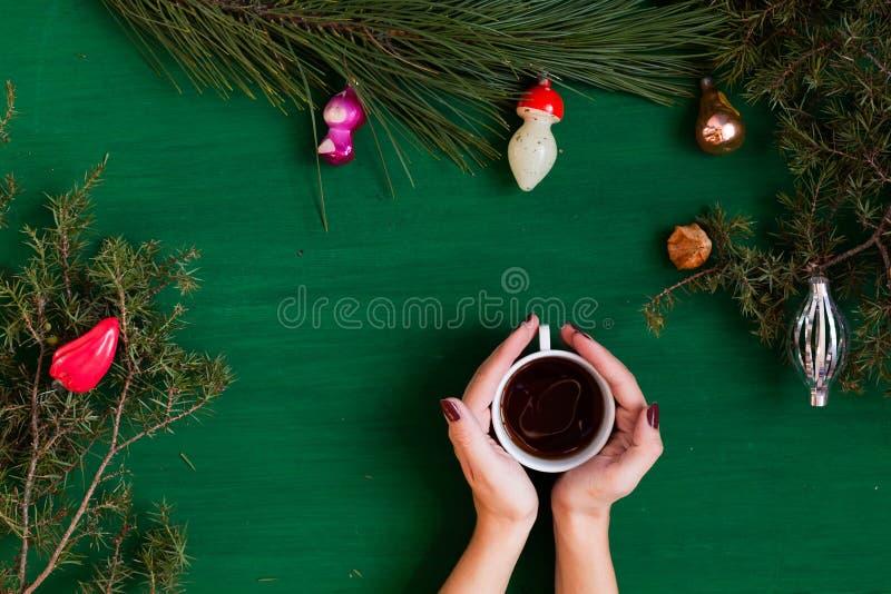 As mãos das mulheres guardam o fundo do café do feriado do ano novo do Natal da árvore de Natal do presente foto de stock