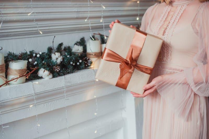 As mãos das mulheres que guardam um presente no papel de embalagem Conceito do Natal fotografia de stock royalty free